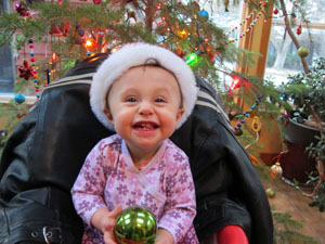 Gianna at Christmas Holding an Ornament and Grinning